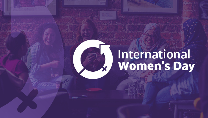 Text reading International Women's Day and the International Women's Day logo over a background image of a group of women.