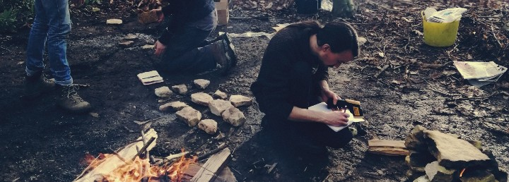 Taking notes by a campfire