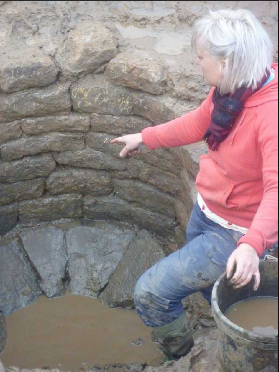 Archaeologist pointing at well at end of its investigation showing stone base and coursed stone lining (Source: OnSite Archaeology).