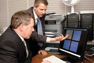 photo of Martin Bates with Rt Hon John Denham MP, explaining how computer simulation can help us understand the properties of liquid crystals.