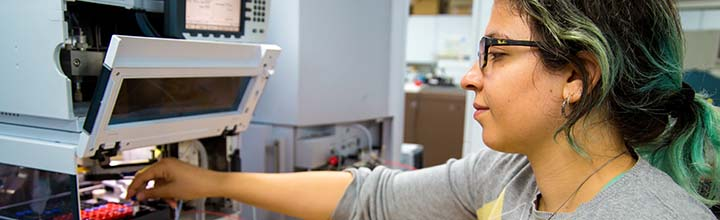 Female PhD student carrying out mass spectrometry. Photo: Baluga Photography