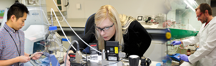 Three chemistry PhD students working in laboratories
