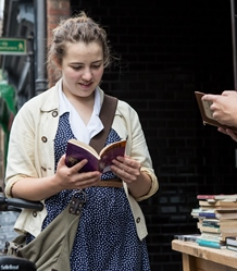 An English student reads a book from a stall in the city centre.