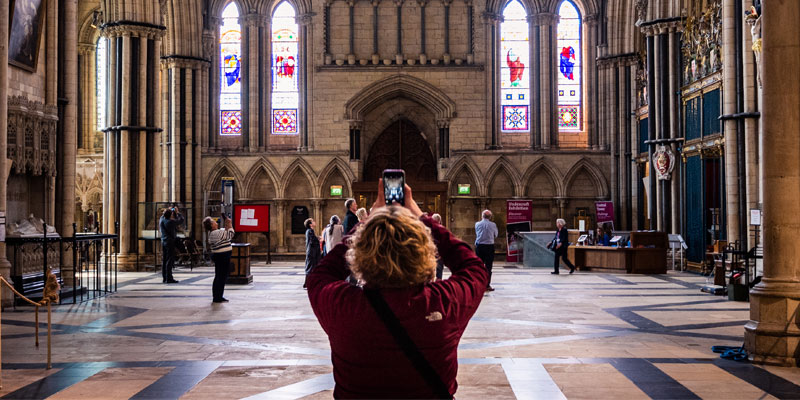 Woman taking a photo of a stained glass window inside a church.