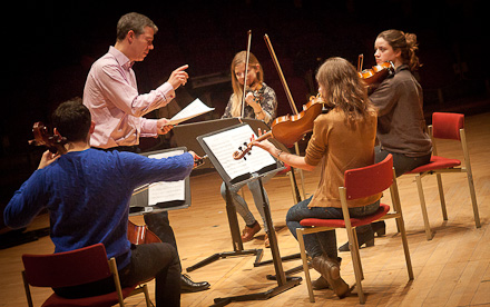 A student group taking part in a performance workshop with a member of Department Ensemble-in-Residence, Quatuor Diotima