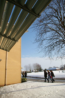 Students walk past building in snow