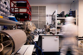 Photo of equipment and a person in a full protective suit in a clean laboratory in Physics.