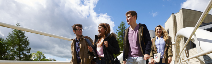 Four students crossing a bridge near the library in the sunshine.