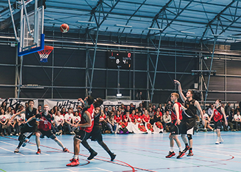 A student scoring a goal in basketball at the opening ceremony of Roses 2017.