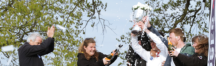 Students lift the Carter James Trophy in victory as champagne is opened in celebration.