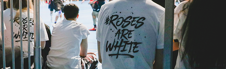 The backs of students watching a basketball game, their T-shirts saying in black on white writing: Roses are White.