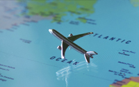 A miniature metal plane rests on a map of the world, over the Atlantic ocean.