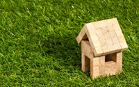 A wooden toy house on grass.