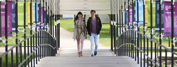 Two students walking across bridge