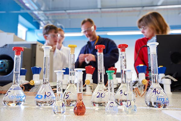 Students in a chemistry lab with an array of flasks.