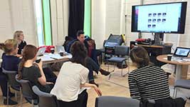 A group of students and staff reviewing a rehearsal together with the project's lead investigators.