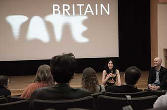 A photograph from a screening of some of the work of the Enhancing Audio Description project at the Tate Britain. The photo features a crowd putting questions to Mariana (the Principal Investigator).